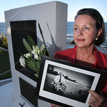 Helen Milne holds a photo of her father, Dick Medcalf, a survivor of the Centaur naval disaster, at the Centaur memorial on Kings Beach. Photo: Michaela O'Neil/174706