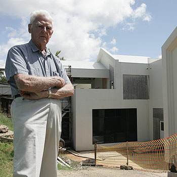 Lloyd Laity pictured outside his neighbour's incompleted mansion home last year. Photo: David Thomas