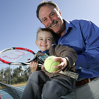 John Newcombe shows his grandson Charlie Tramacchi, three, the finer points of tennis at the opening of the new tennis court at Caloundra City School, Pelican Waters. Photo: Chris McCormack/174887