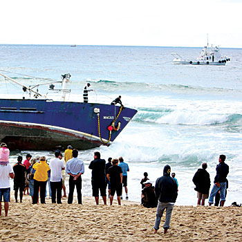 More than 100 people were on Buddina Beach yesterday to witness the recovery of the long liner Magus, which ran aground on Friday night. Photo: Jason Dougherty/ 174954e