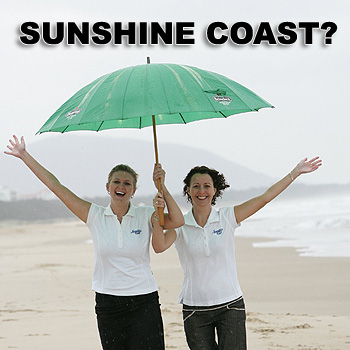 Lauren McAtamney and Gemma O'Brien from Tourism Sunshine Coast are not perturbed by the wet weather on Mudjimba beach. Photo: Chris McCormack/175063