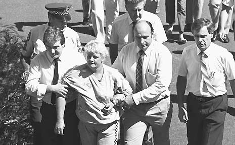 Valmae Fay Beck is escorted by police after the murder of 12 year old schoolgirl Sian Kingi.