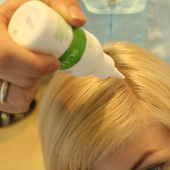 Nioxin's Aaron Batchelor applies the Scalp Renew treatment to a client at Halo of Mooloolaba.
