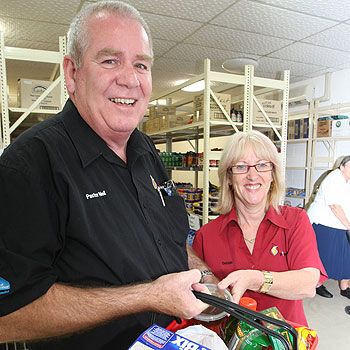 Executive pastor Neil Cooper of Gateway City Church, Caloundra and co-ordinator Debbie Knight with some of the cheap food items available to Centrelink cardholders at their Gateway Care affordable grocery shopping centre in Bulcock Street. Photo: Nicholas Falconer/175008