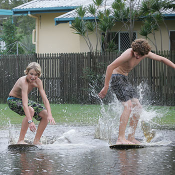 Gordon Sykes, 15, left, and Owan Vandevorst, 14, play on their skim boards in Maroubra Street at Maroochydore, after heavy rain drenched the Coast. Photo: Brett Wortman/175145