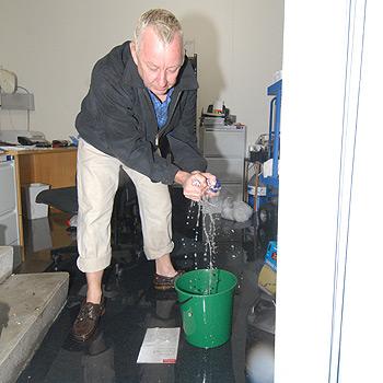 Santorini Resort manager Roy Vandermeer cleans up his office after flood waters made their way inside. Photo: Warren Lynam/175134