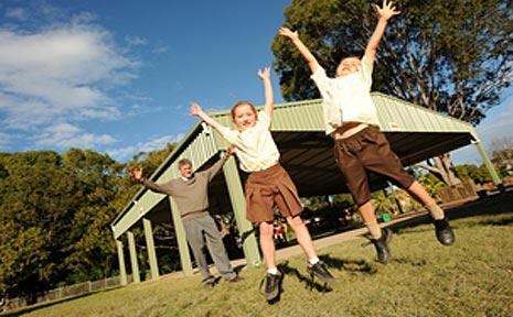 Narranga Public School students and the principal jump for joy over new hall.