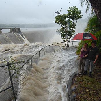 Shane Radaich and Sara Burston from Yandina watch the water flow over Wappa Dam during Monday's deluge. Photo: Warren Lynam/175134