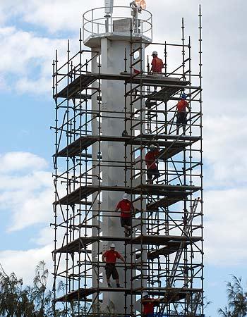 Workmen erect scaffolding around the shipping beacon at Golden Beach in preparation for repair work. Photo: Warren Lynam/175309