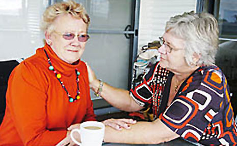 Margaret Maynard (left) is comforted by host Wendy Reynolds after the theft of a handbag containing 15 rings, stolen from the Reynolds' verandah.