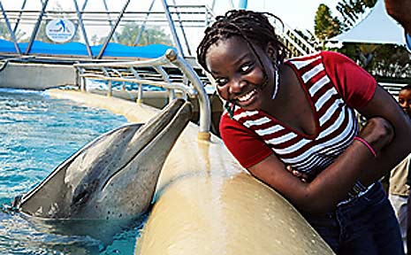 Esther Mokey, a refugee from the Congo, gets a kiss from a new friend at the Pet Porpoise Pool.