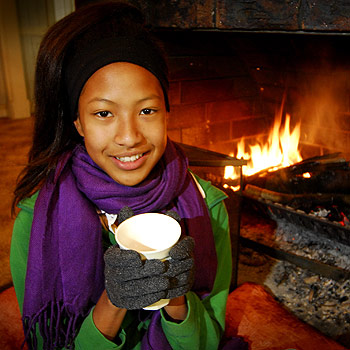 Piyusha Yamaoka, 13, of Maleny, warming up with a hot chocolate in front of the fire. Photo: Che Chapman/175619