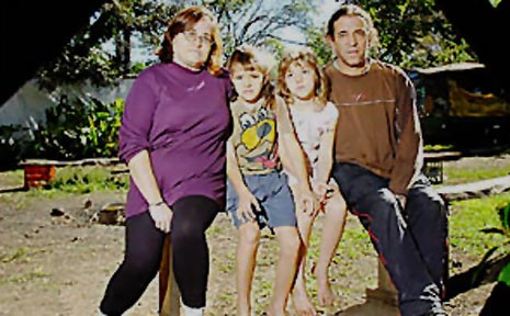Wendy and Adrian Ryan with daughters Khy, 8, and Khrystal, 7, in their Nimbin yard where a homemade bomb blew up.