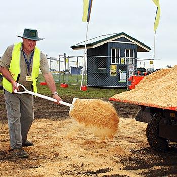 Farm Fantastic director Geoff Mazlin lays sawdust to keep the roads around the event site dry. Photo: Vicki Wood/C12526