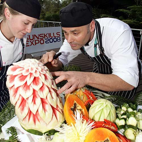 Sunshine Coast TAFE master chef Darren Sansrini shows apprentice Chloe Hall the skill involved in fruit carving. Photo: Jason Dougherty/177035c
