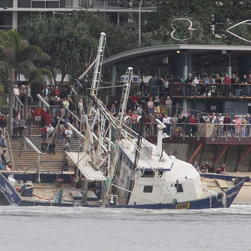 A crowd looks over the trawler Miss Melissa on Mooloolaba Beach just before it was successfully removed. Photo: Cade Mooney/ 177290
