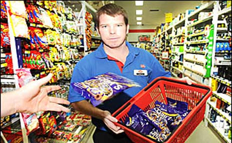 IGA Goonellabah supermarket manager Gareth Morahan removes Cadbury Chocolate Eclairs from shelves yesterday.