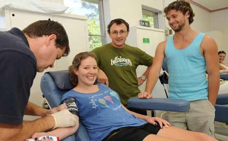 Alex Person and Joel McCafferty watch on as Mia Yore donates blood.