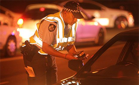 Police conduct a random breath test on a motorist.