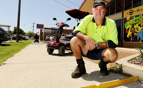 PATHS MEASURE UP: Ballina Shire Council employee Michael Barton takes some footpath measurements outside the Ballina Scooters shop in Tamar Street, Ballina.