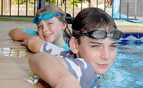 Kayla, 8, and Asten Jago, 9, cool off in their family pool, which is fitted with a fence and ensures that their safety is a top priority when swimming.