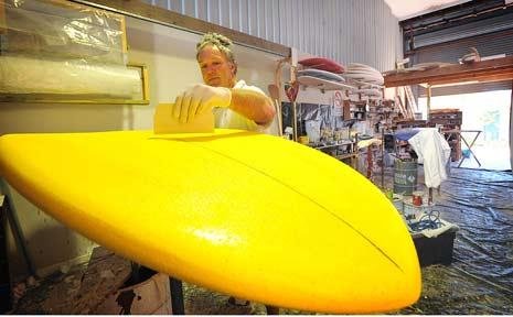 Rod Hocker works on a surf board.