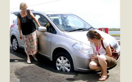 Margaret Rose (left) and daughter Jess check out their Nissan Tiida hatchback, which sunk into the roadway in Moon Street, Ballina, yesterday.