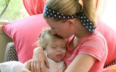 Kelly Ryan comforts her daughter Artemissia at their Burringbar home.