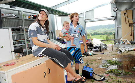 Lesley McQueen and Troy Garred with their son Che, 11 months, in the destroyed shed where Troy was isolated from his trapped family.