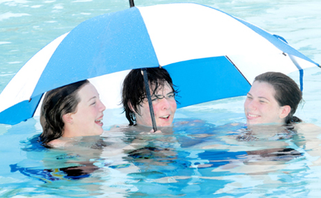 Chantal Thomas, Brad Dailey and Kylie Hansen, of Mackay, cannot decide if they want to be wet or dry during a shower of rain at the Bluewater Lagoon yesterday.