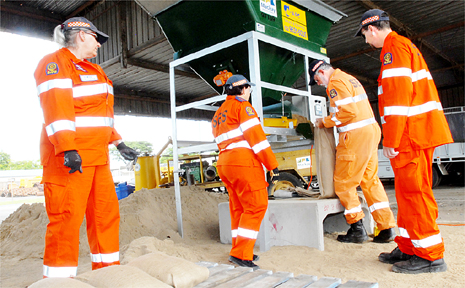 Elwyn Cameron, group leader Gail Bennett and Nev Ross use the new sand bagging machine while Leslie Loughnan looks on.