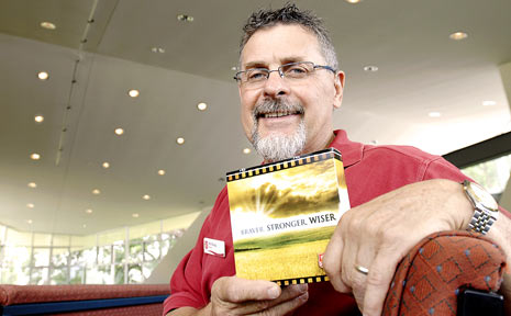 HOPING FOR BETTER TIMES: Salvation Army captain Phil Sharp holding a free DVD for people who suffer, or may know someone who is suffering, from depression because of their financial situation.