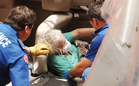 Emergency service workers cut an elderly woman out of her wrecked car.