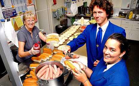 Ruben Brown, Jordan Pedrou and Gail Swan help make hot dogs for the Coffs Harbour High School Victorian bushfire appeal.