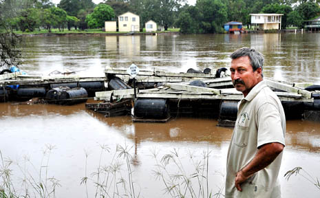 Oyster grower John Lindsay inspects his flood-damaged oyster rafts.