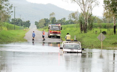 A 27-year-old driver is stranded on the top of his ute at the Sandy Creek crossing on Marian-Eton Road as emergency service personnel consider how to rescue him.