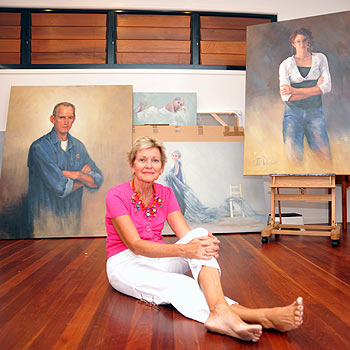 Coolum artist Jan Williamson relaxes in front of a display of her paintings. Photo: Warren Lynam/181218