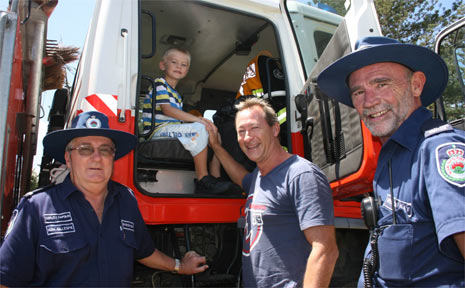 Bayley Fallon, 6, gets to sit in the driver's seat of the Byron Bay Rural Fire Brigade's fire truck in Apex Park on Sunday. His dad, Mark Fallon, is pictured with deputy captain, Ken Gillespie (left) and Gregg Miller.