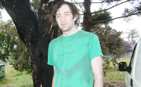 Alex Naughton under the tree blackened when his borrowed car was set on fire and destroyed.