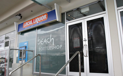 The masked gunman robbed the Beach Bottle Shop at around 10.40am.
