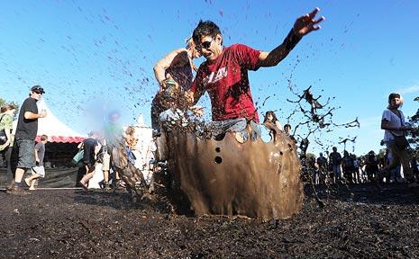 Matthew Pratt and Sera Haewera having fun as they frolic in the muddy conditions at Bluesfest.