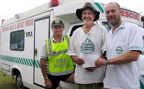 Byron Bay Farmers Market manager Donald Recsei (centre) hands over the quarterly cheque for $1300 to Mark Gasson (right) and Tim Breen of Brunswick Valley Rescue.