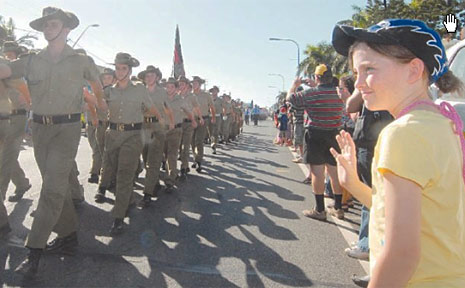 Danielle Burns, 12, waves to marchers as Mackay's main Anzac Day parade moves down Gordon Street on Saturday.