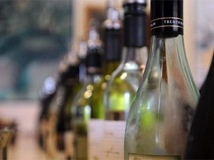 Alleged a man threatened a cashier with a wine bottle