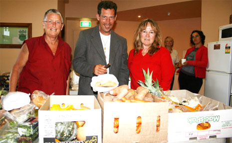 Liberation Larder organiser Honu Dawson (left) and volunteer Wendy Jagger (right) help Michael O'Hagen with a bag of free groceries.