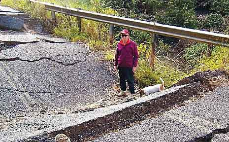 Zutano Close resident Frank Cairnes inspects the collapsed culvert on East West Road.