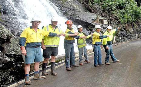 Workers point the way now that Waterfall Way is open.