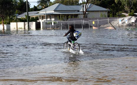 A cyclist pedals through floodwaters in Ewingsdale Road near Kendall Street last week.