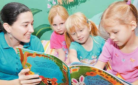 Carlisle College Early Learing Centre assistant Nadine Keioskie reads a story to Jordan Ballingall, 4, Dearna Levin, 3, and Jorja Wilson, 4.