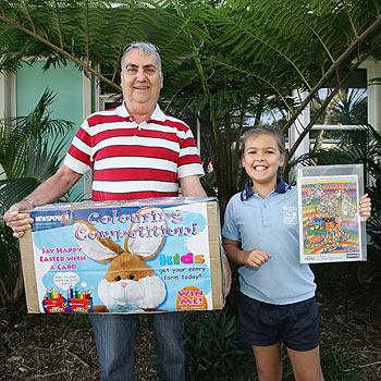 Newsagent Lance Barrett presents Coolum Primary School student Tajana Jenkins with her prize. Photo: Mike Garry/scw1547